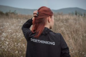 "Redhead wearing a black jacket with ""Overthinking"" on it."