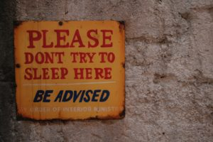 "A plaque reading ""Please Don't Try to Sleep Here...Be Advised"""