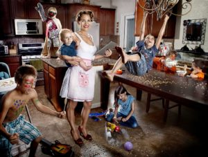 single mom in her kitchen surrounded by kids destroying her house and working from home